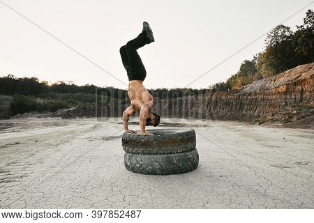 Healthy Young Man With Athletic Body Using Two Heavy Tyres For Sport Activity At Sand Pit. Muscular