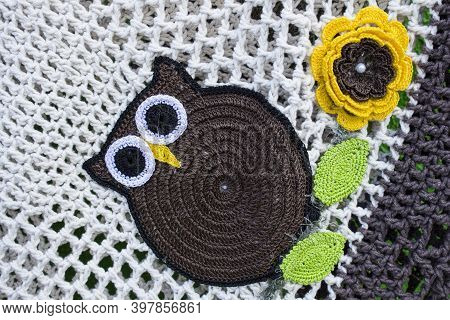 White Crochet Piece With Brown Owl Next To A Yellow And Brow Flower