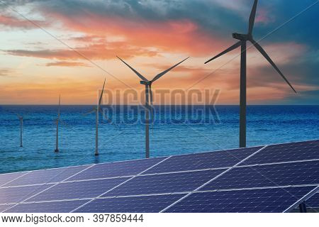 Alternative Energy Sources. Wind Turbines Installed In Water, Solar Panels On Foreground