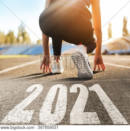 Start New Year With Fresh Vision And Ideas. Sporty Woman Ready For Running Near 2021 Numbers On Road