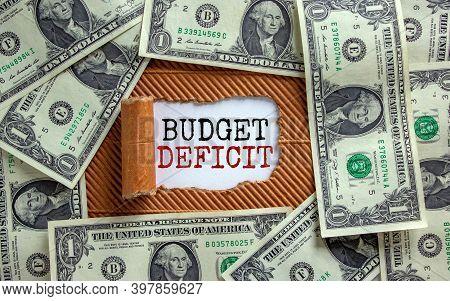 Budget Deficit Symbol. The Words 'budget Deficit' Appearing Behind Torn Brown Paper. Dollar Bills. B