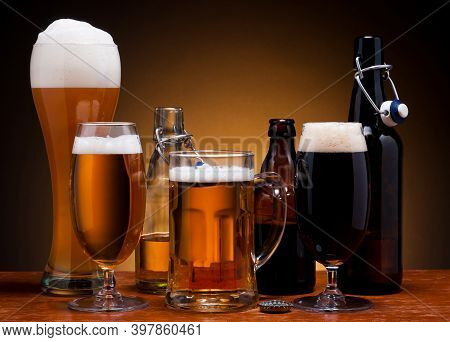 Various Sorts Of Draft Beer In Bottles, Glasses And Mug On Wooden Table. Fresh Brewed Beer With Hops