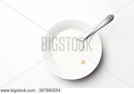 Flat lay white cereal bowl with spoon and one piece of cereal floating in the milk. High Key still life with copy space.