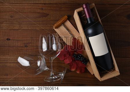 Wine Still Life  A bottle of wine with blank label in a wood box with two glasses, corkscrew, leaves and grapes. Flat Lay with copy space on rustic dark wood table.