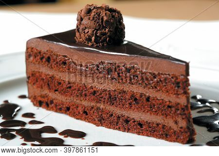 A Delicious Slice Of Chocolate Dessert Cake Is Served On A White Plate And Decorated With Round Chun