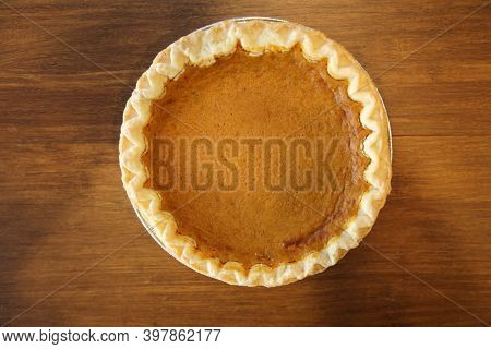 Pumpkin Pie. A while Fresh Baked Pumpkin Pie on a brown wooden table. Pumpkin Pie is enjoyed world wide for holidays and special events.