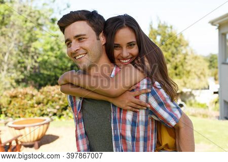 Caucasian couple spending time in a garden. man is holding woman piggy back, looking at the camera and smiling. self isolation during covid 19 coronavirus pandemic.