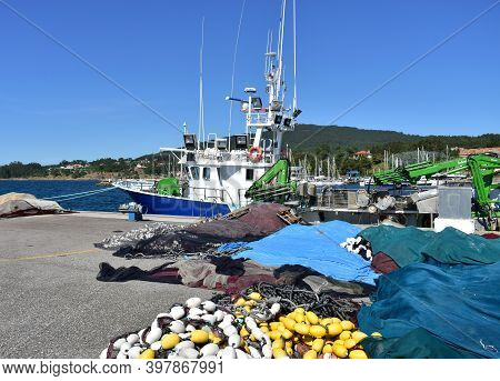 Portosin, Spain. July 3, 2020. Galician Fishing Vessel In A Harbor With Fishing Net At Famous Rias B