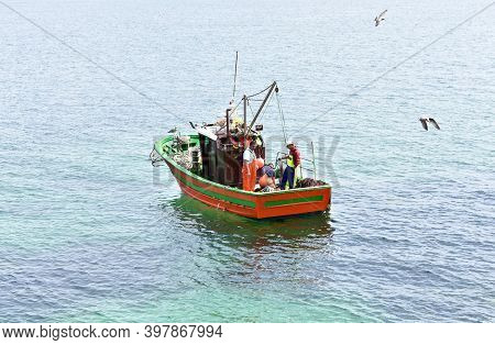 Ribeira, Spain. August 27, 2020. Galician Fishing Vessel On The Sea With Fishermen Working At Famous