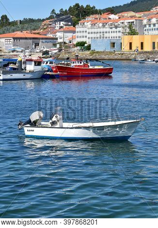 Portosin, Spain. July 3, 2020. Small White Motor Boat Moored In A Harbor With Galician Fishing Vesse