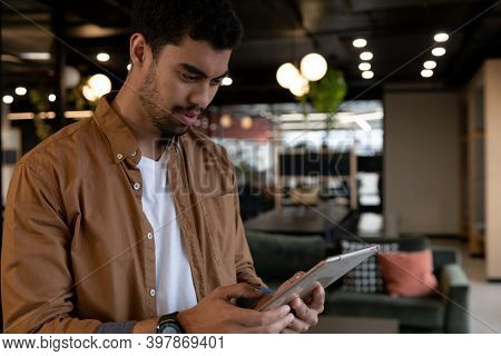 Mixed race businessman using digital tablet in creative office. social distancing in business office workplace during covid 19 coronavirus pandemic.