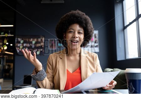 Mixed race businesswoman during video call in creative office, talking. technology and social distancing in business office workplace during covid 19 coronavirus pandemic.