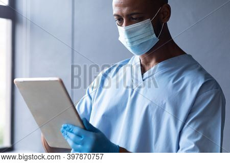Mixed race male doctor wearing face mask using digital tablet. medicine healthcare professional during covid 19 coronavirus pandemic.