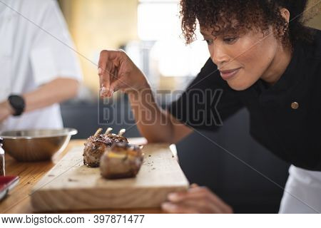 Female african american chef adding salt over grilled ribs on wooden board at restaurant kitchen. food preparation restaurant culinary gourmet