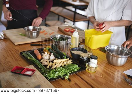Female chef and caucasian male chef in kitchen. trainee chef and female chef standing at a table and preparing food.