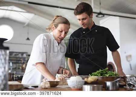 Female chef and caucasian man in kitchen. trainee chef standing at a table listening to female chef.