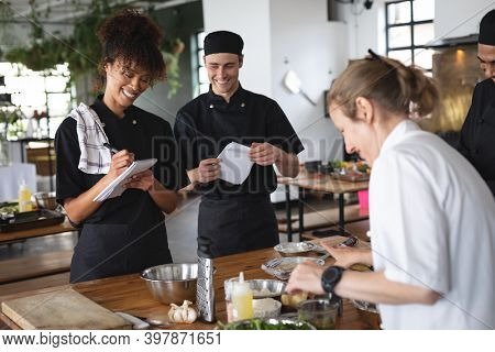 Female chef and divserse group in kitchen. trainee chefs standing around a table listening to female chef.