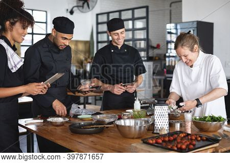 Female chef and divserse group in kitchen. trainee chefs using tablets and standing around a table listening to female chef.