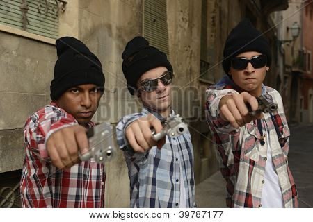 Portrait of gang members with guns on the street