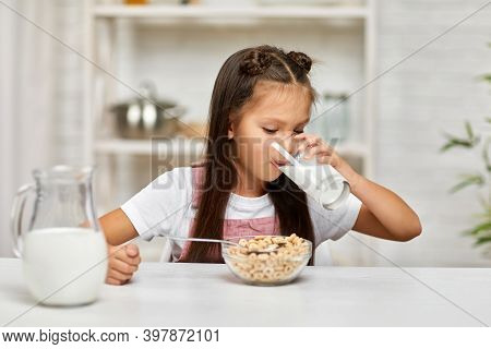 Cute Little Girl Eating Breakfast: Cereal With The Milk. Child Drinking Milk In The Kitchen. Healthy