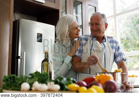 Senior caucasian couple wearing aprons embracing each other while cooking in the kitchen at home. social distancing quarantine lockdown during coronavirus pandemic