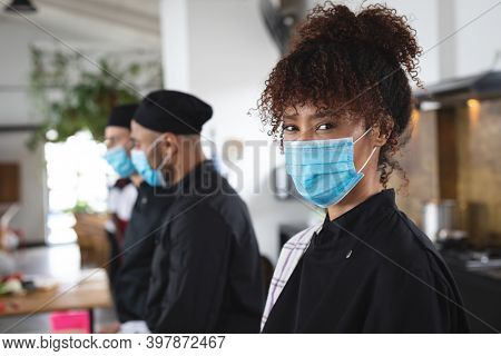 Divserse group wearing face masks in kitchen. portrait of trainee female chef looking at camera. hygiene in professional kitchen during coronavirus covid 19 pandemic.