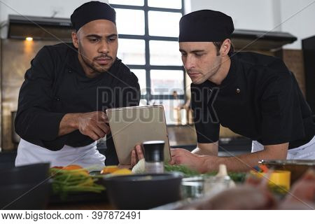 Two divserse male chefs in kitchen. two trainee chefs standing at a table and using tablet.