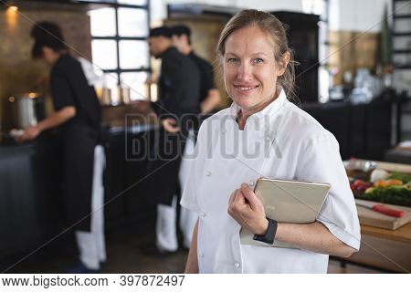 Female chef and divserse group in kitchen. portrait of female chef looking at camera, holding tablet, with diverse group of trainee chefs preparing food in the background.