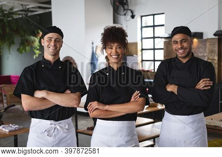 Portrait of diverse male and female chefs standing with hands crossed in restaurant kitchen. food preparation restaurant culinary gourmet