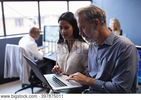 Diverse man and woman working together in creative office, using laptop. creative business office teamwork.