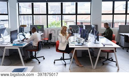 Caucasian woman working in creative office, putting virtual reality headset on. modern office business technology.