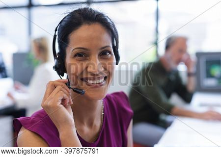 Portrait of mixed race woman wearing phone headset in modern office. communication and social distancing in business office workplace during covid 19 coronavirus pandemic.