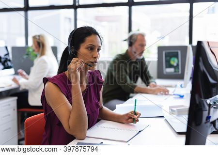 Mixed race woman wearing phone headset in modern office. communication technology customer service modern office business.