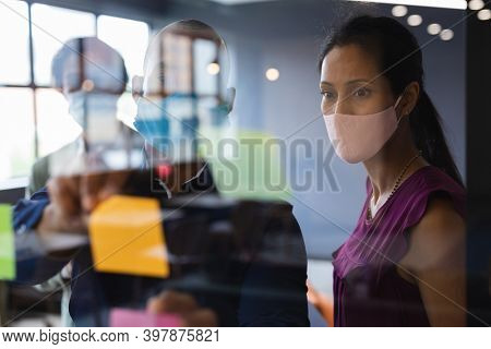 Diverse business people wearing face masks writing on glass board in office. social distancing in business office workplace during covid 19 coronavirus pandemic.