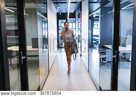 Smiling african american woman walking talking on smartphone in office. social distancing in business office workplace during covid 19 coronavirus pandemic.