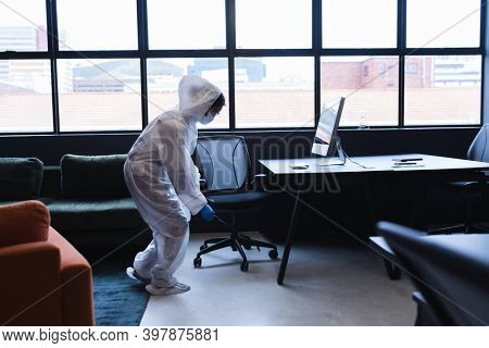 Health worker in protective clothing spraying disinfectant in office. hygiene protection in business office workplace during covid 19 coronavirus pandemic.