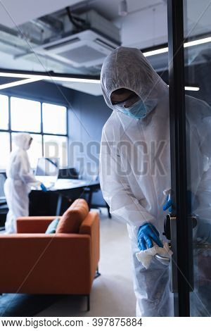 Health workers in protective clothing disinfecting creative office. hygiene protection in business office workplace during covid 19 coronavirus pandemic.