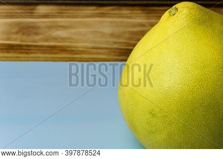 Close-up Of A Yellow Pomelo On A Blue Background. Free Space For Entering Text. Pomelo Fruits On A B