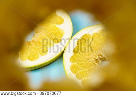 Look Through A Piece Of Pomelo At A Sliced Pomelo On A Blue Background. Close-up Of Pomelo Slices.