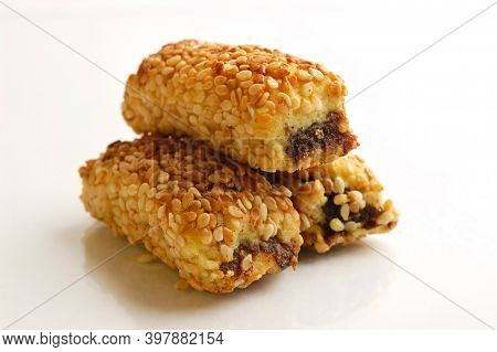 Appetizing eastern sweet dates filled cookies mamoul sticks covered with sesame Isolated on white background