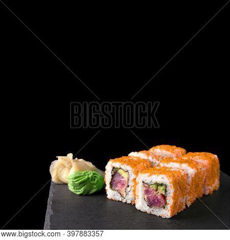 California Tuna Roll In Orange Tobiko Roe Isolated On Black Background. Japanese Cuisine Sushi Set W