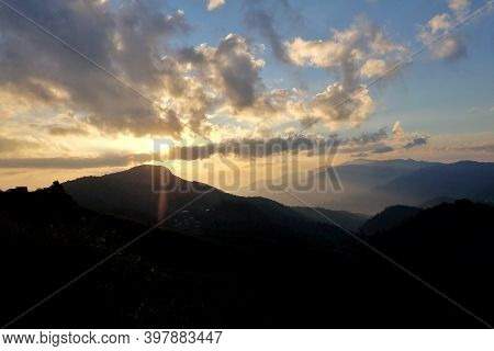Blurred Silhouette Sunrise Over A Mountain Against Blue Sky White Clouds In The Morning With A Shado
