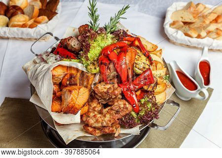 Mixed Grill Meat, Fried Vegetables And Grilled Salmon Fish Fillets Decoration In Warm Dish. Assorted