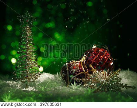 Red Christmas ornament and a shiny Christmas tree on dark green background with falling snow. Winter holidays, new year concept.