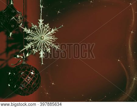 Shiny gold and red Christmas ornament on dark red background in faded colors. Winter holidays, new year concept.