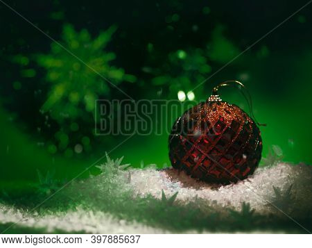 Red Christmas ornament on moody dark green background with snow. Winter holidays, new year concept.