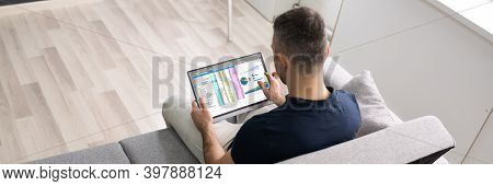 Man Using Spreadsheet Data On Tablet Computer