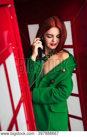 Redhead Girl In A Green Coat Talking On The Phone In A Red Phone Booth 4