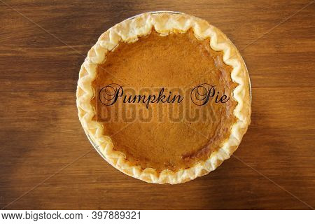 Pumpkin Pie. Fresh Baked Pumpkin Pie with Pumpkin Pie text across the front. Pie on a brown wooden table.