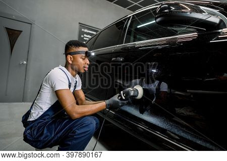 Young African Man Working At Car Detailing Service, Polishing Black Car With Orbital Polisher To Eli